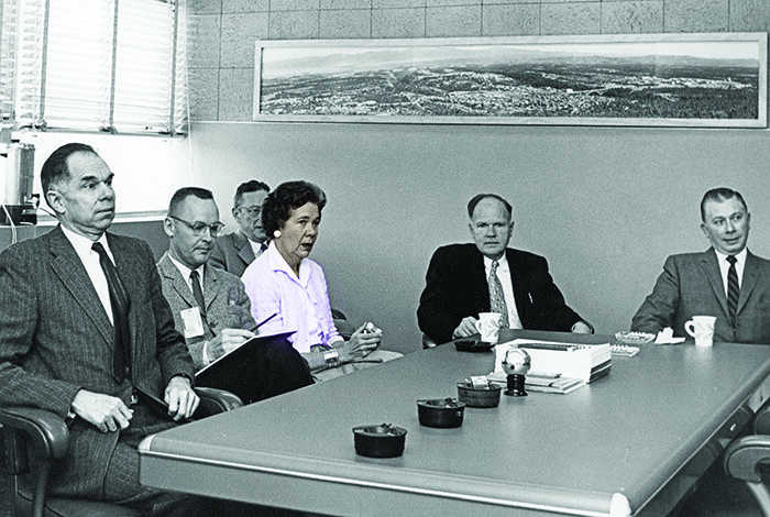 A woman and several men sit around a table in a conference room.