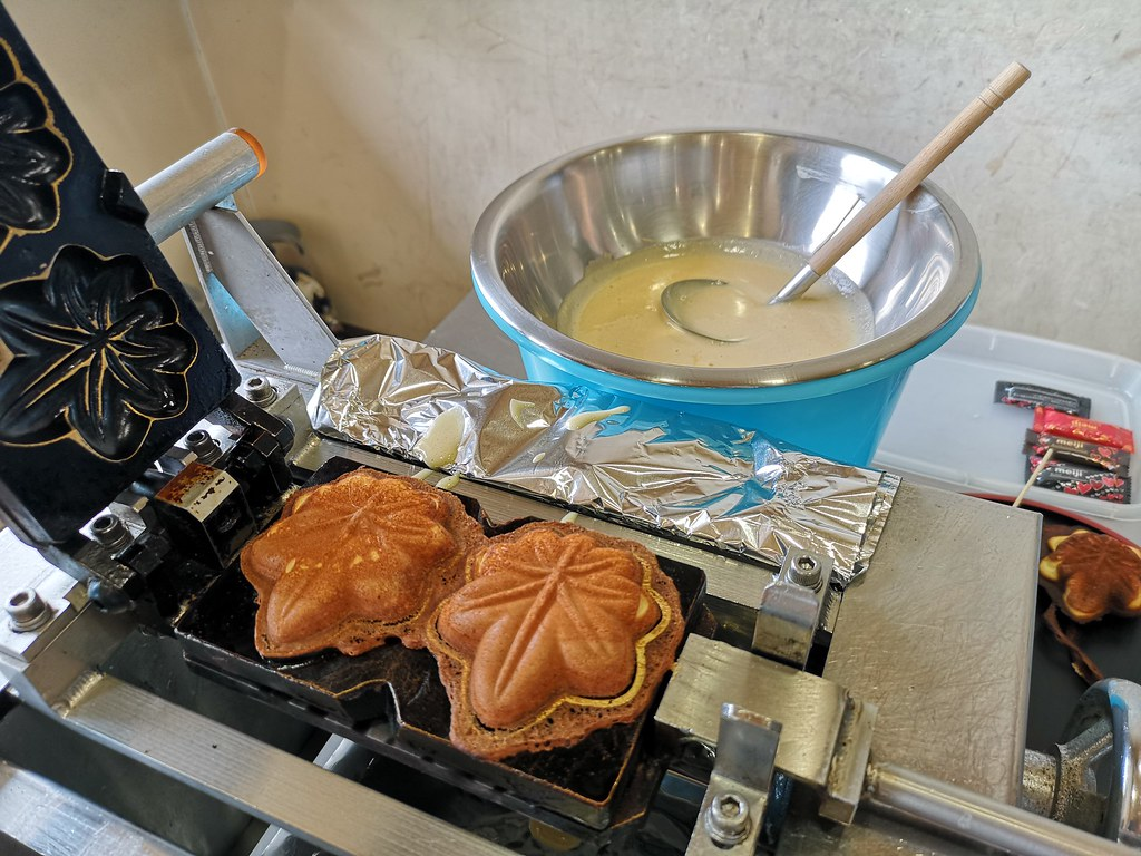 Making maple leaf-shaped cakes, which are similar to the popular snack taiyaki. There is no maple syrup in the batter or filling. Fun fact: Japanese maple trees do not produce maple syrup.
