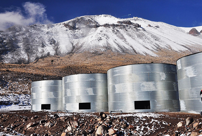 The High Altitude Water Cherenkov (HAWC) Gamma-Ray Observatory, located 13,500 feet above sea level on the slopes of Mexico's Volcán Sierra Negra with three silver large tanks in front of snowy mountains