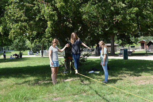 One student walks a slackline, while two others watch