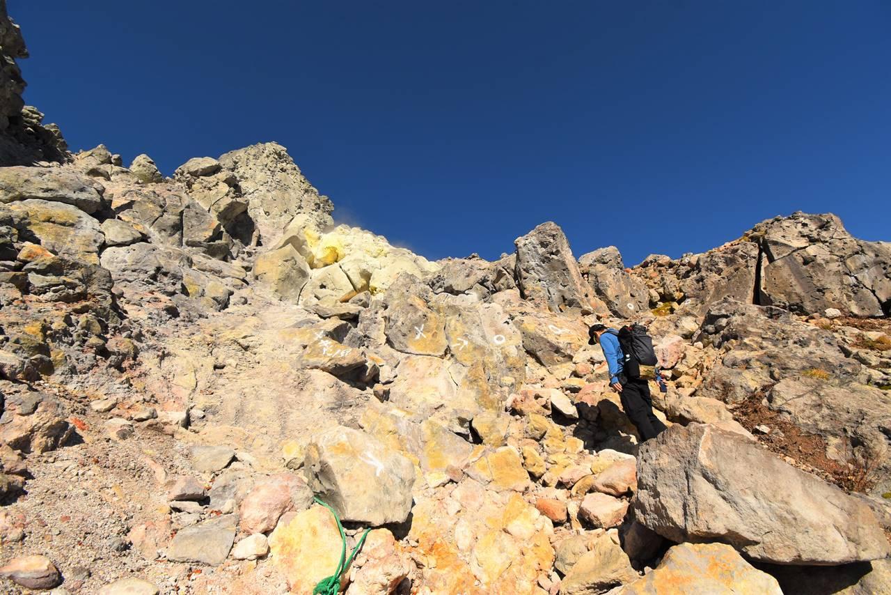 硫黄臭と噴煙が立ち込める焼岳山頂の岩場