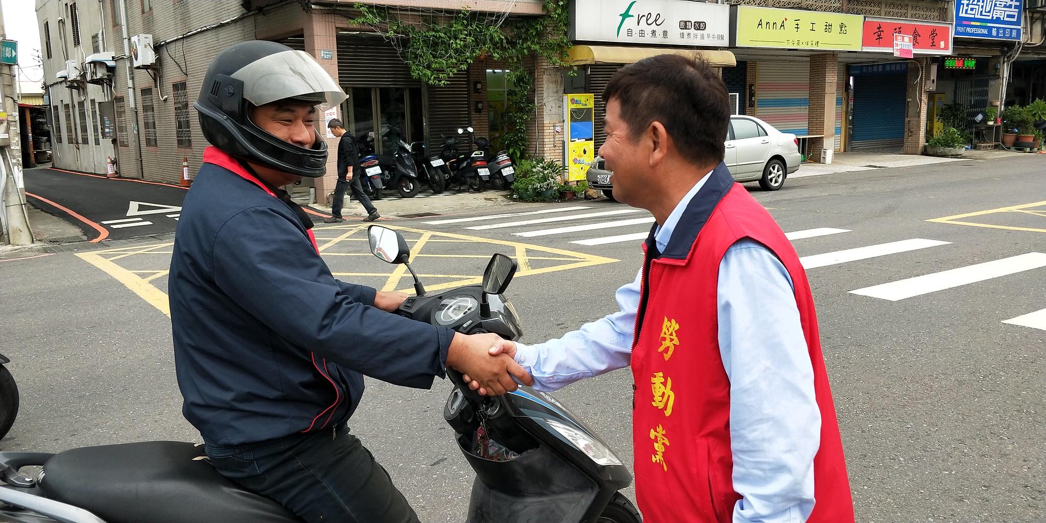 罗美文(右)在街头与上下班的民众互动。(罗美文竞选总部提供)