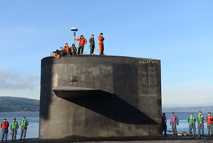 Men in life vests stand atop a submarine.