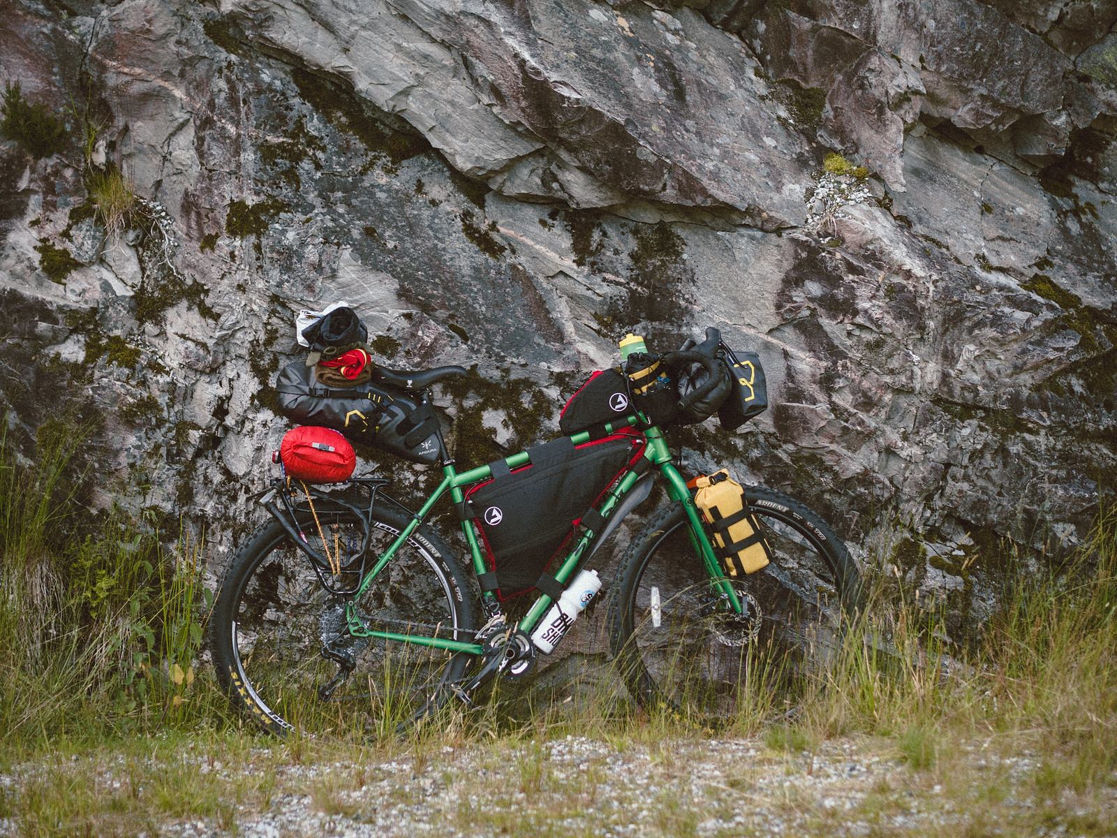 loaded touring bicycle leaning against rock