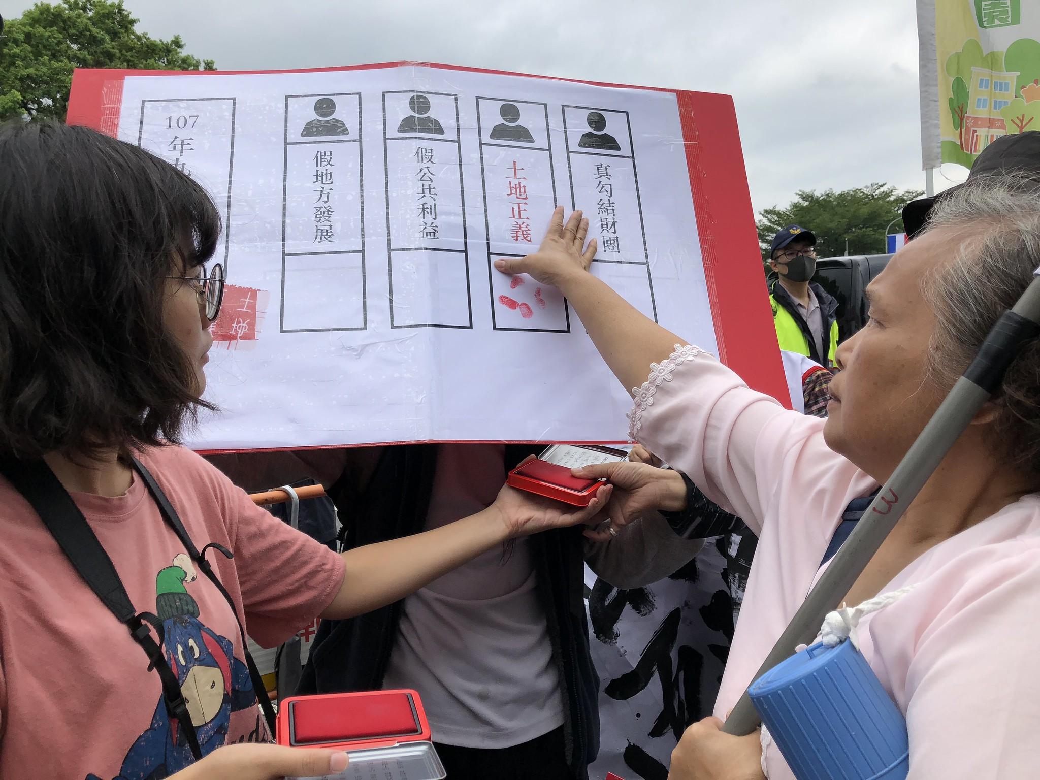 聯盟在凱道前準備了紅色印泥與票券道具,各地自救會按手印投「土地正義」一票。(攝影:王顥中)