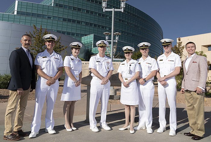 A group of men and women in white uniforms stand outside in front of the NSSB.