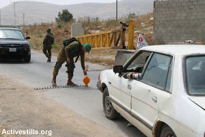 以色列士兵於接近約旦河西岸的檢查哨查看巴勒斯坦民眾的車輛。(圖片來源:Ahmad Al-Bazz/Activestills.org)