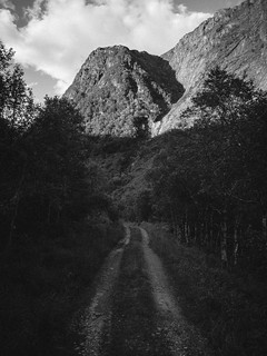 black and white photograph of a shaded road leading into a valley, sunlit mountaintop above.