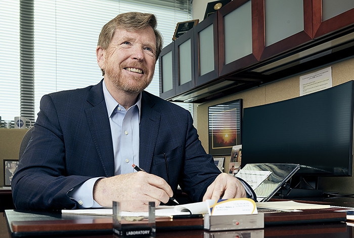 A man sitting at a desk smiles at the camera.