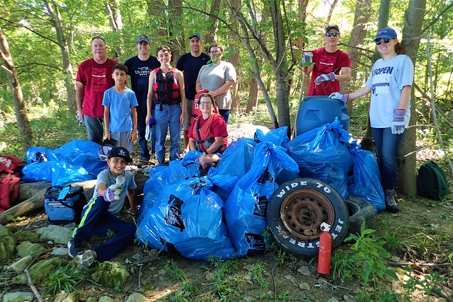 A gorup of volunteers in front of their large trash haul!