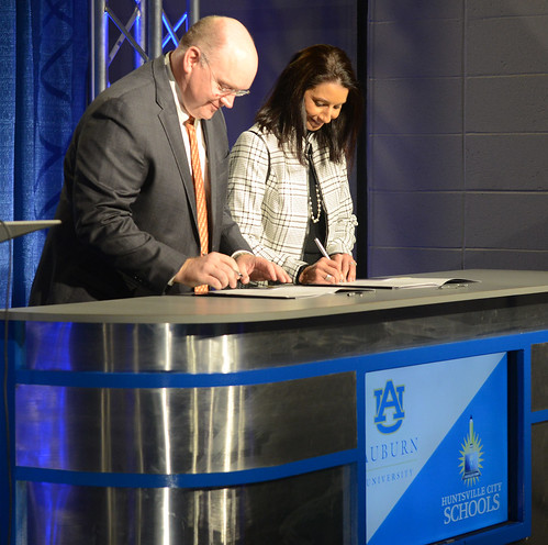 Christopher B. Roberts and Christie Finley signing a document
