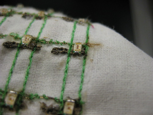 smd soldering on machine embroidered circuit | by leahbuechley