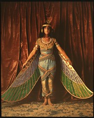 Dancer wearing Egyptian-look costume with wings reaching to the floor | by George Eastman House