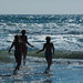 Mother and two daughters run into ocean