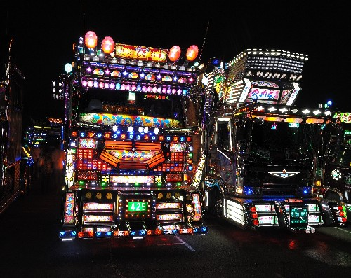 Two Dekotora trucks lit up before a dark sky