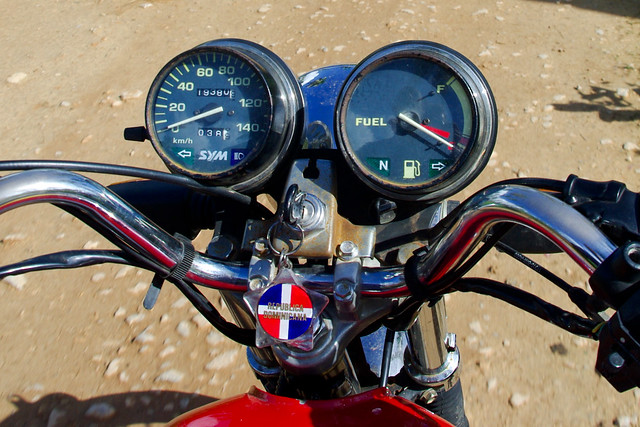 Como Una Moto: Handlebars and dash of a motorcycle driving over a dirt road. The key in the ignition has a star-shaped keychain with the Dominican flag and text reading Republica Dominicana.
