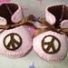 pink and brown baby booties with peace sign motifs