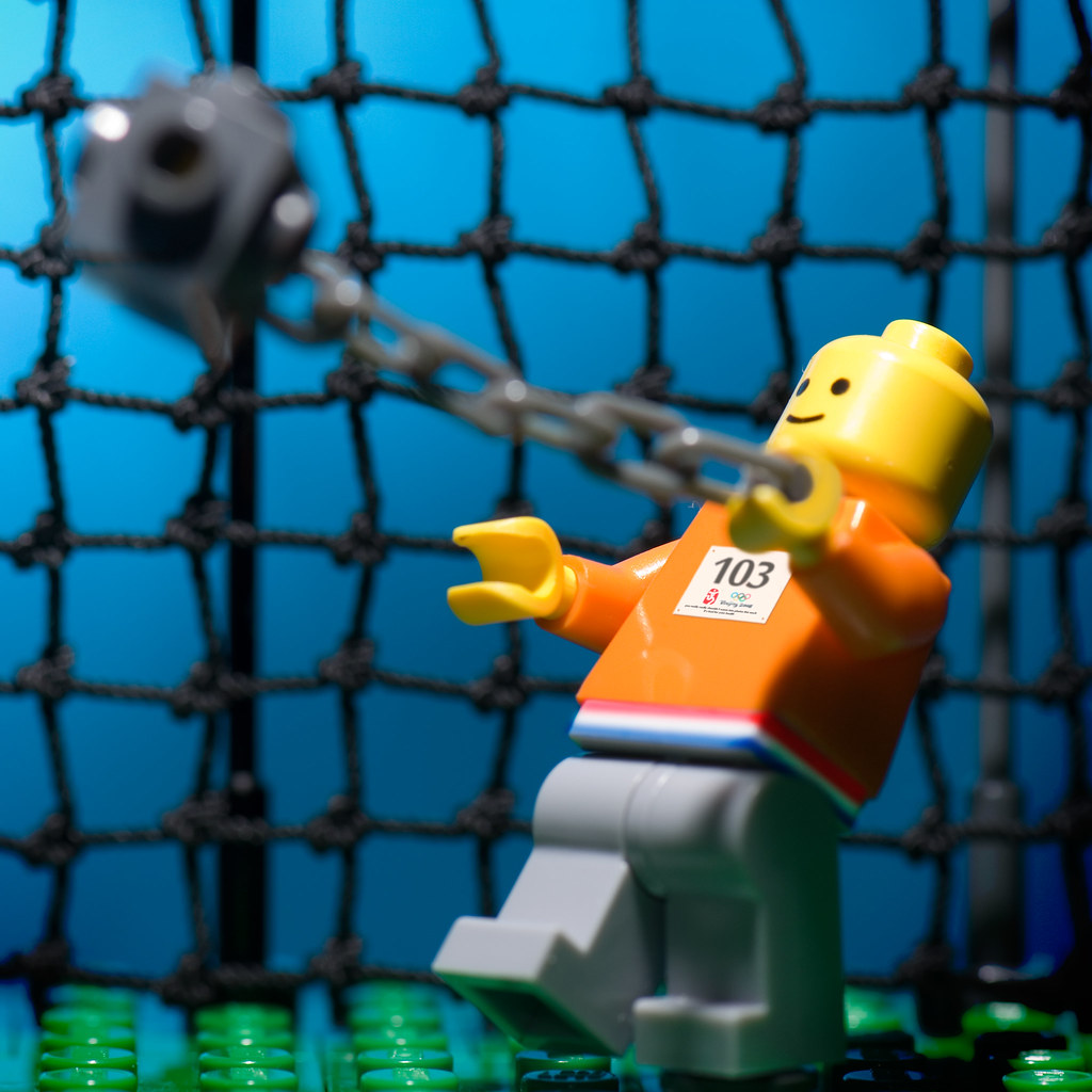 a description of the athletic event of hammer throw as a metal ball attached to a wire and handle The olympic hammer throw is a throwing event where the object is to throw a heavy metal ball attached to a wire and handle the name hammer throw comes from an older contest where men threw a sledge hammer.
