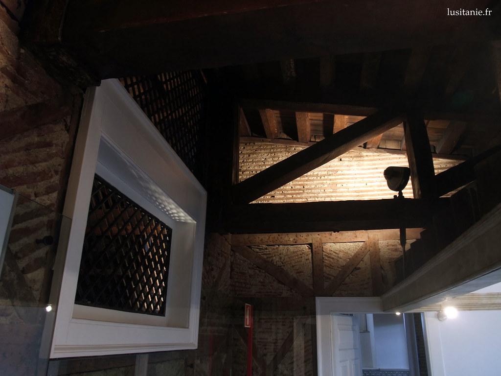Charpente et briques, au dernier étage du bâtiment