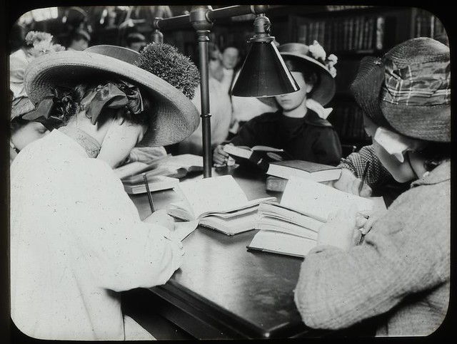 Vintage image, girls in straw hats and old fashioned dresses read and write around a library table