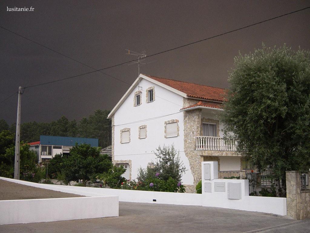 Nous sommes en plein jour dété, et le ciel est noir, contrastant avec la blancheur des maisons