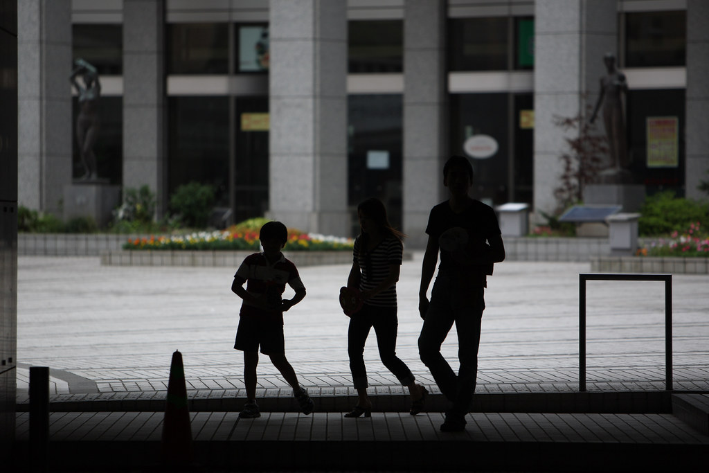 Silhouettes of three children standing outside a building (photo credit: mrhayata)