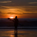 Surfer Girl in Silhouette, standing with her surf board while totally mesmerized by the golden sunset