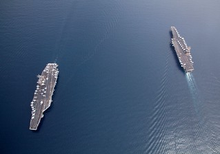 The Navy's oldest aircraft carrier, right, passes the Navy's newest aircraft carrier | by Official U.S. Navy Imagery