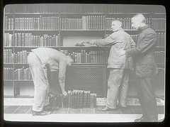 Three men at dusting books, one bent over | by New York Public Library