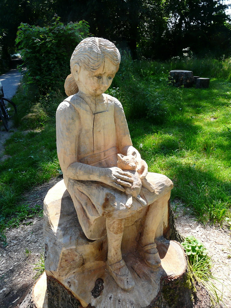 Girl sitting on a tree stump there are many carved