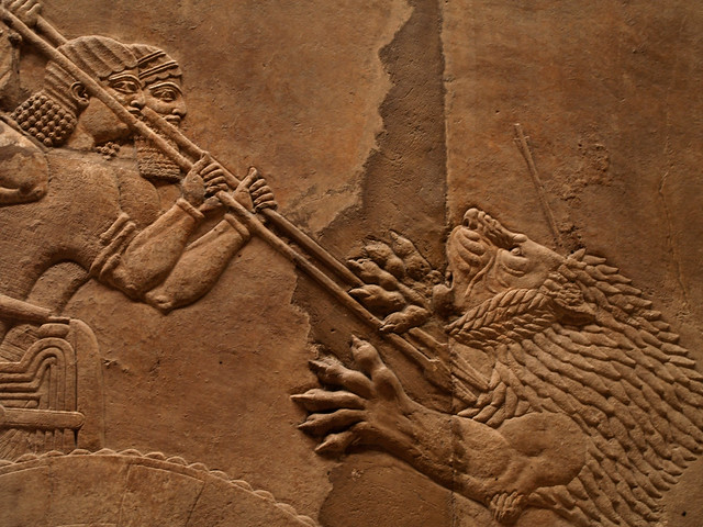 Assyrian relief carving men spearing lion closer