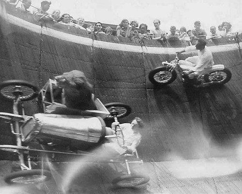 people racing in a motorcycle and a go-cart with a sidecar with a lion in it on a vertical wall-of-death. | by Foxtongue
