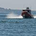 Coast Guard boat (orange) enters harbor at full speed in Morro Bay, CA