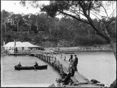 Rough wooden bridge over river, group with dog on the shore | by Powerhouse Museum Collection