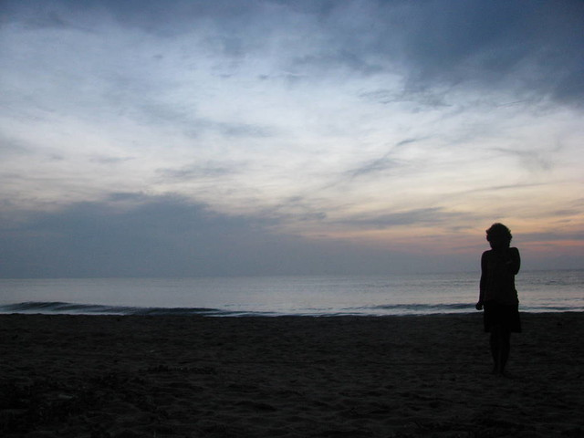 Silhouette of Woman on Phone on Beach at Sunrise