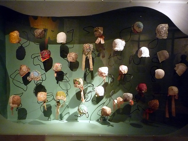 Needlework display hats in the museum of art and design for Baseball cap display ideas