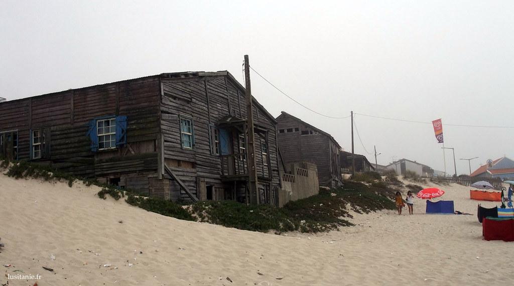Maisons de bois en ruines au bord de la mer, sur le sable