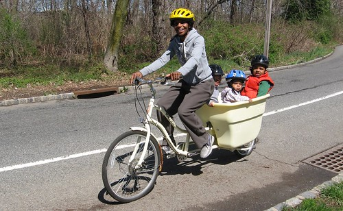 African-American woman toting three children in a Dutch style bicycle, Newark