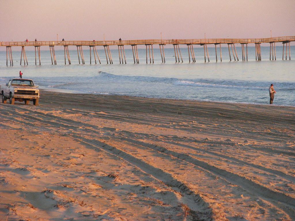 Outer banks sunrise surf fishing fisherman having a cast for Outer banks surf fishing