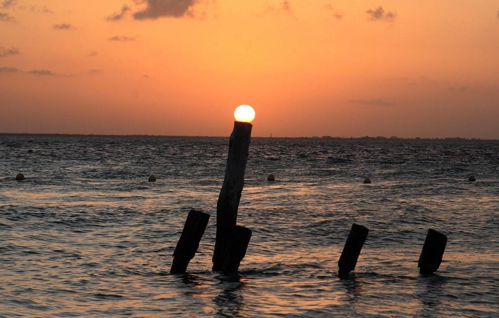 Explore The Beauty Of Caribbean: Sun Resting On A Post Near Playa Norte, Isla Mujeres