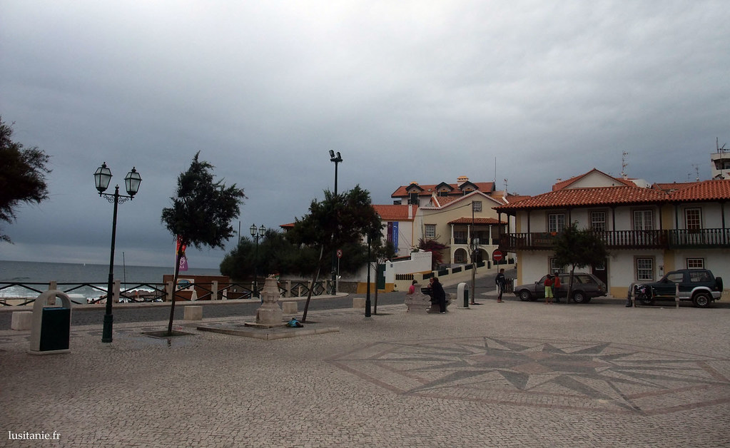 Place du village avec sa rose des vents pavée sur les trottoirs
