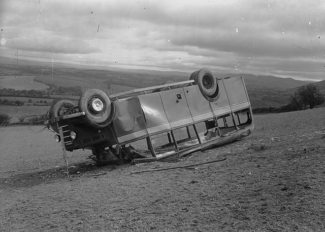 Image of a Bedford bus on its roof in a field - 'Coach accident' from the P B Abery Collection at the National Library of Wales