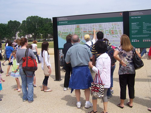 People looking at the new National Mall wayfinding signage at the Smithsonian Metro station