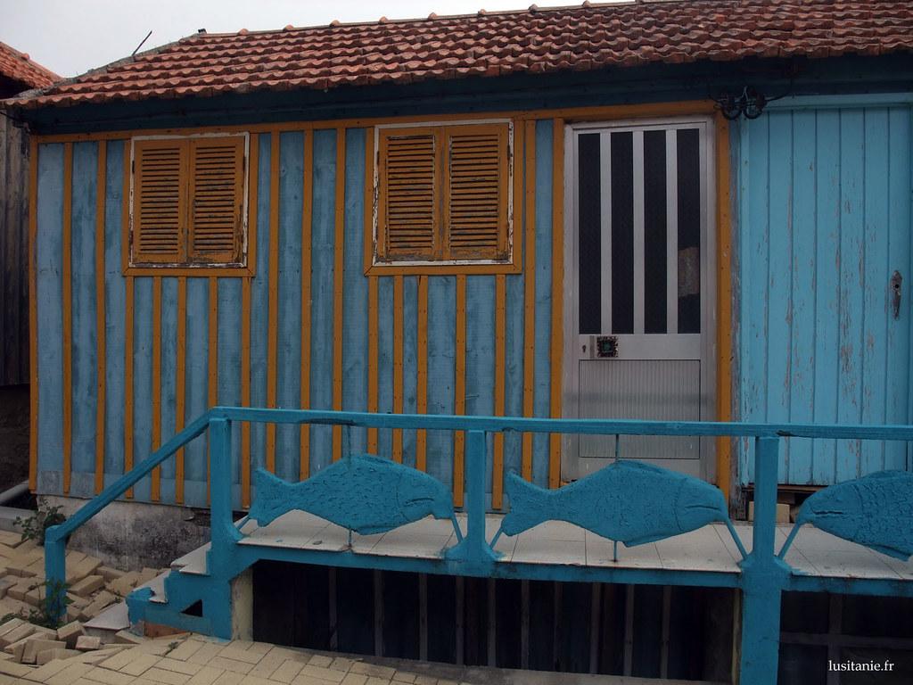 Maison bleue, avec une porte en aluminium, et une vieille porte en bois