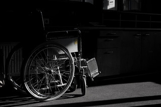 Wheelchair partially in the shadow | by Marcel Oosterwijk
