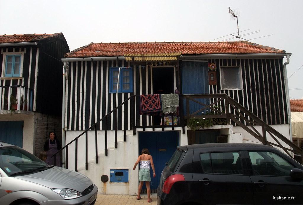 La maison est très colorée, avec sa porte et sa fenêtre bleues, et ses murs rayés
