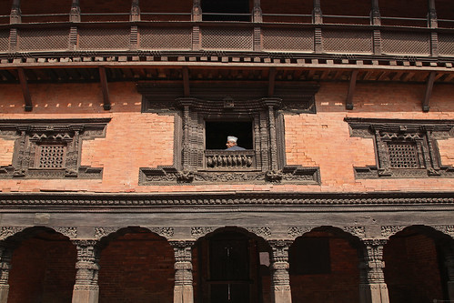 Man looks out of window on to a courtyard in Kathmandu | by World Bank Photo Collection