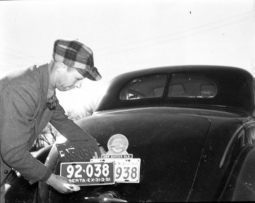 Unidentified Man Changing His Automobile License Plates | by Galt Museum & Archives on The Commons