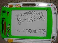 A kid's magnetic doodle pad with incorrect equations scrawled on.