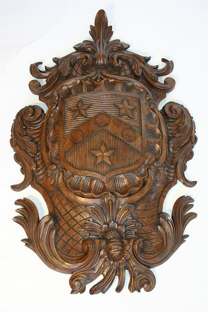 A large hand carved coat of arms this walnut finish on